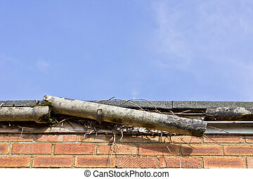 Broken gutter - A broken plastic gutter on the roof of a...