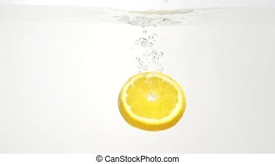 Parts of the lemon and water splash in slowmotion