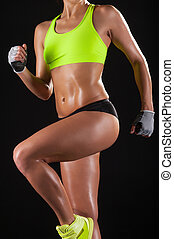 Sporty body. Cropped image of young woman in sports clothing posing against black background