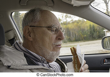 senior man with expressive face eating fast foods in his car...