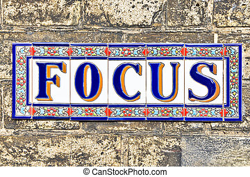 Focus spelt with decorative tiles on a brick wall