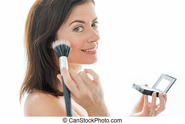 attractive woman in her forties applying makeup - portrait...