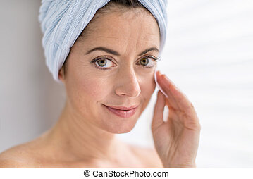 attractive woman in her forties removing make up - portrait...