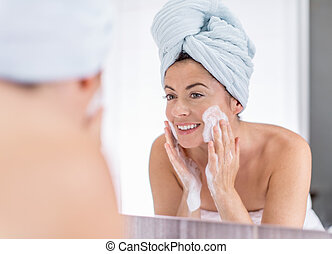 middle aged woman cleaning her sking over the sink -...