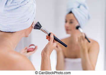 middle aged woman applying makeup - portrait of a beautiful...