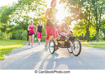 active mother jogging - Woman pushing her little girl in a...