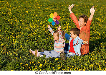 Spring sun worshipers - woman with kids on the flower field
