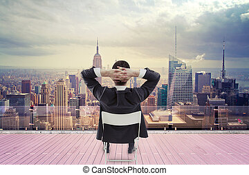 businessman looking at city - businessman sitting on roof...