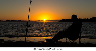 Sunrise Fishing_dng - Man stitting by his surf-caster rod,...