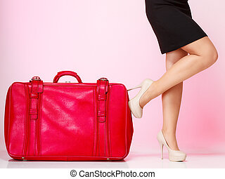 Side view woman legs with red suitcase on pink background -...