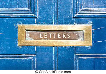 Letterbox - A metallic letterbox in a blue wooden door