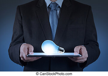 businessman using tablet computer growing  light bulb as concept