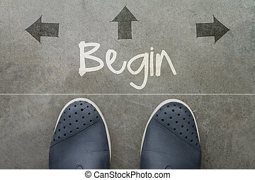 Hand drawn BEGIN design word on front of business man feet...