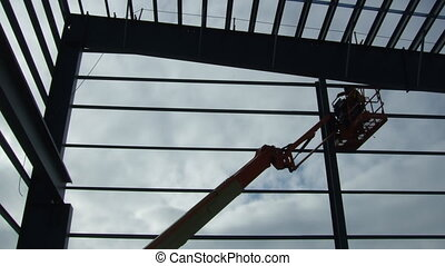 ironworker erecting structure with aide of crane