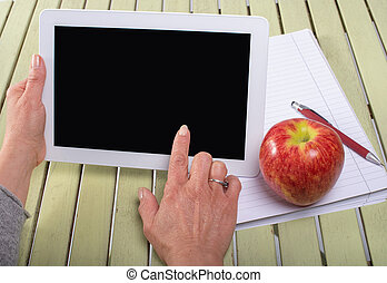 Woman holding a tablet computer with an apple