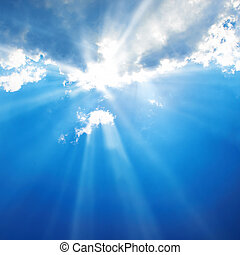 Beautiful blue sky with sunbeams and clouds. Sun rays.