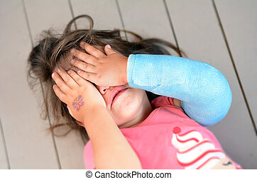 Abused little girl with a broken arm covering here face...