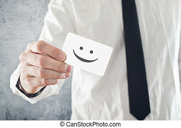 Businessman holding business card with smiley face printed....