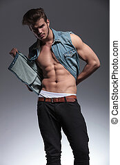young man pulls his jeans vest - attractive young man pulls...
