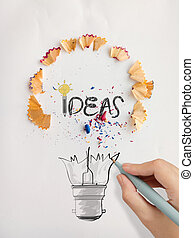 hand drawn light bulb word design IDEA with pencil saw dust on paper background as creative concept