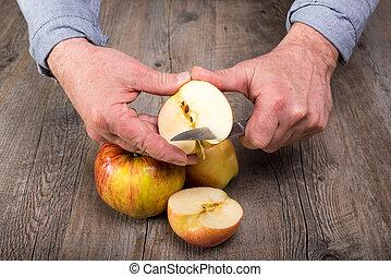 Hands of a man cutting an apple - Hands of senior man...