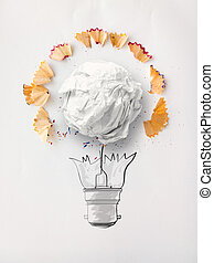 hand drawn light bulb and crumpled paper with pencil saw dust on paper background as creative concept