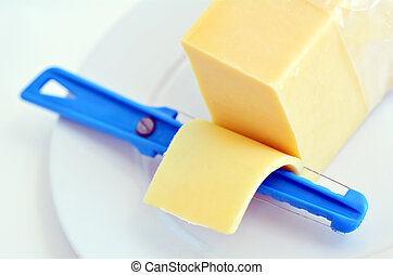 Yellow cheese slice and Cheese slicer on a white plate...
