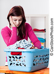 Bored woman and box with laundry - Bored young woman and box...