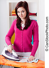 Smiling woman during ironing laundry at home