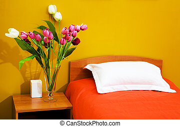 bed with an orange coverlet - Beautiful tulips at a bed with...