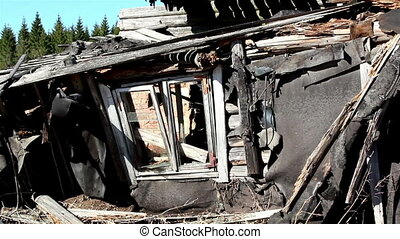 A destroyed wooden house with broken glass on the window