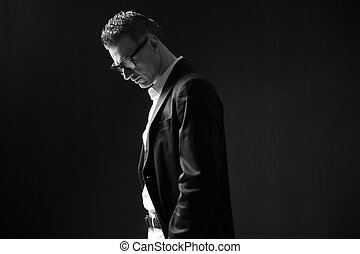 Black and white photo of a thoughtful businessman in glasses