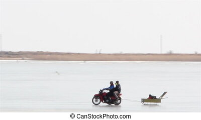 A motorbike used for fishing on the snowy area