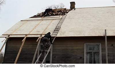 Roofers putting some wooden shingles on the roof - Roofers...