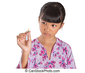 Young Girl And Medicine Tablets - A young Asian Malay girl...