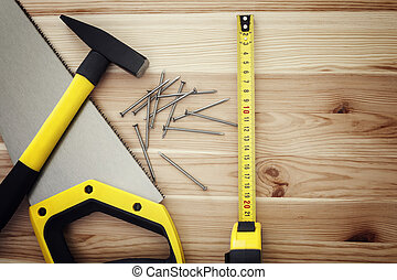 Hammer, nails, saw and tape measure on wood