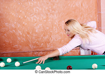 Blonde in pink playing billiards - Young blonde woman in...