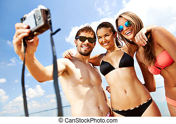 Summer moment - Portrait of happy friends taking photo of...