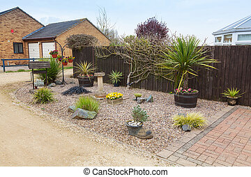 Urban rockery garden with grasses and shrubs. - Rockery...