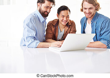 Working with laptop - Smiling men in casual using laptop