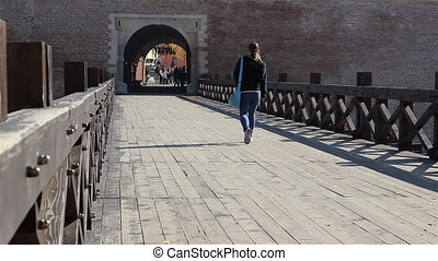 Girl Walking on Old Bridge