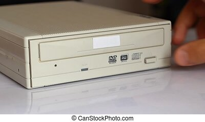 Inserting Disc into DVD ROM Device - Person inserts a DVD...