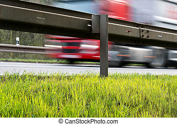 Guardrail - a crash barrier and roadside with going trac