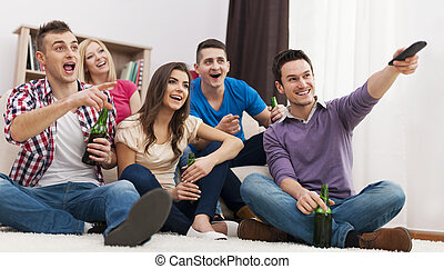 Happy friends watching funny movie at home