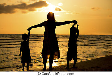 Happy family have fun on beach at sunset