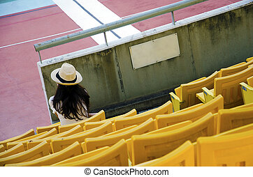 Grandstand on the stadium with the woman sits.