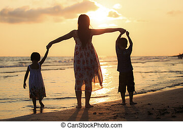 Mother with her daughter and son on the beach