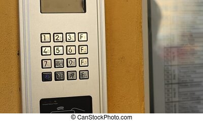 Calling on Doorphone - Woman is pressing the keys of an...