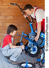 Boy helps his father mounting a cultivator machine - Boy...