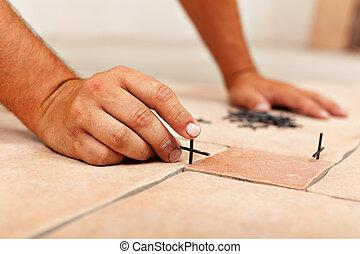 Worker hands placing spacers between ceramic floor tiles -...